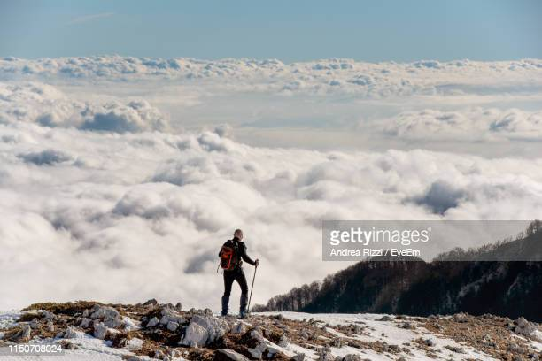 man standing on land against cloudscape during winter - andrea rizzi stock pictures, royalty-free photos & images