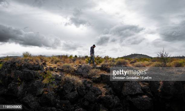 man standing on land against sky - christian soldatke stock pictures, royalty-free photos & images