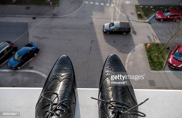 man standing on ledge above street - ledge stock pictures, royalty-free photos & images