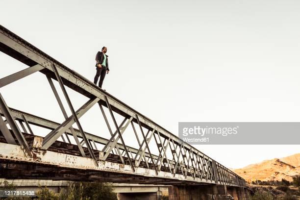man standing on metal bar of an old railway bridge - selbstmord stock-fotos und bilder