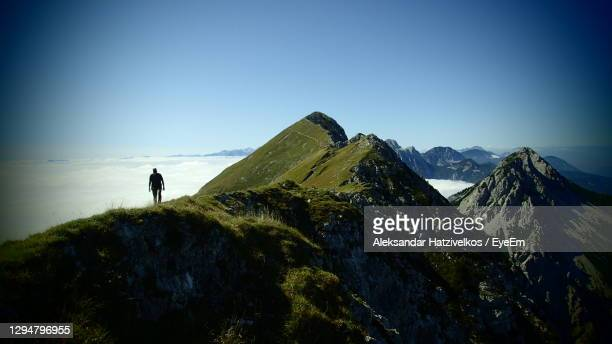man standing on mountain against clear blue sky - kranj stock pictures, royalty-free photos & images