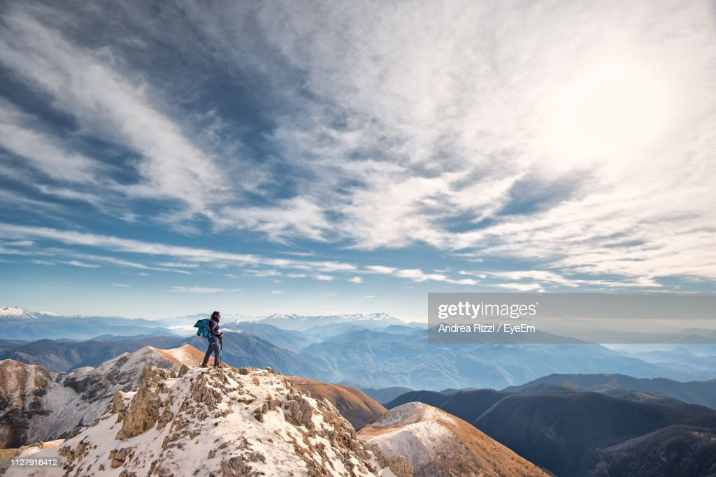 Man Standing On Mountain Against Cloudy Sky During Winter : Stock Photo