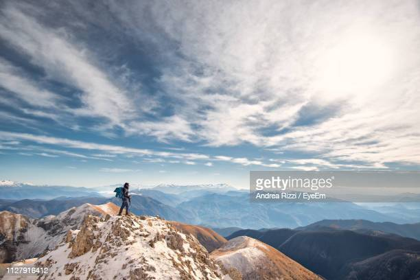 man standing on mountain against cloudy sky during winter - andrea rizzi stock pictures, royalty-free photos & images