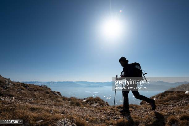 man standing on mountain against sky - andrea rizzi stockfoto's en -beelden