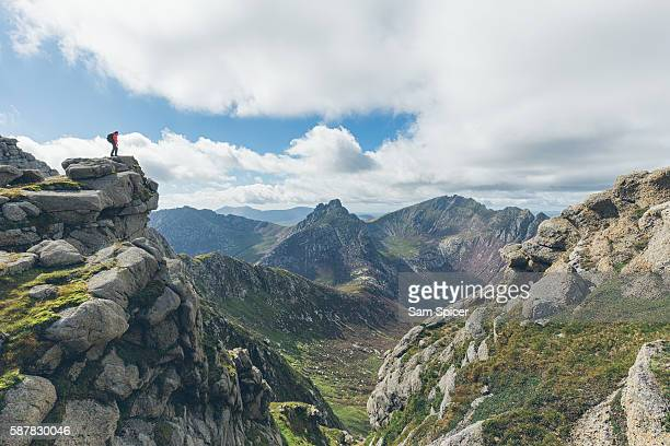 Man standing on mountain summit looking at epic Highland vista