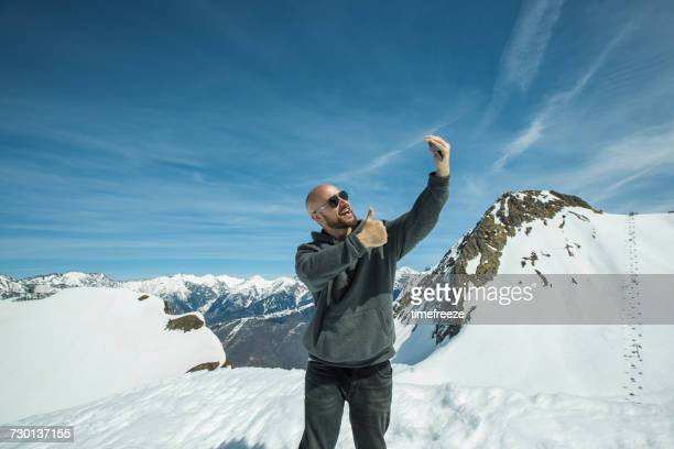 man standing on mountain summit taking a selfie, chamonix, france - one man only stock pictures, royalty-free photos & images