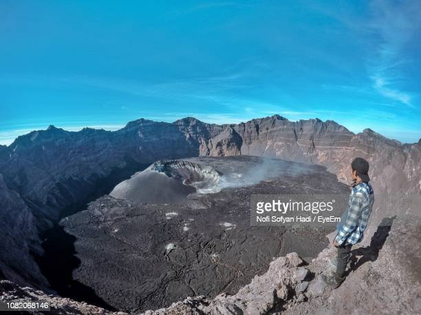 Man Standing On Mountain While Looking At Volcanic Crater