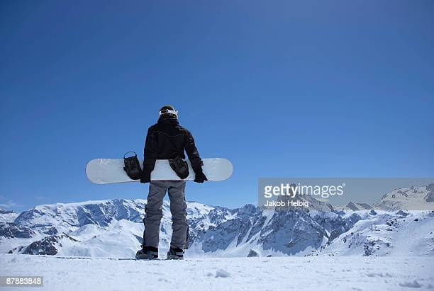 Man standing on mountain with snowboard