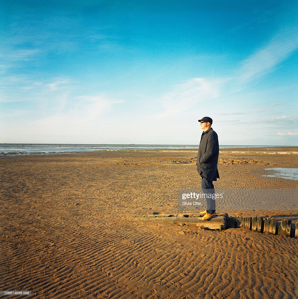 man standing on mudflats, side view : Photo