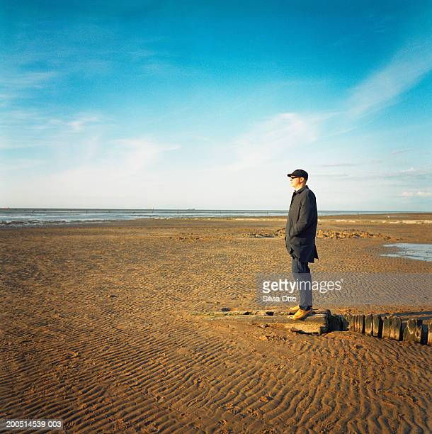 man standing on mudflats, side view
