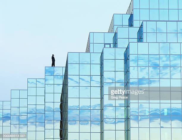 man standing on office building roof (digital composite) - high section stock pictures, royalty-free photos & images