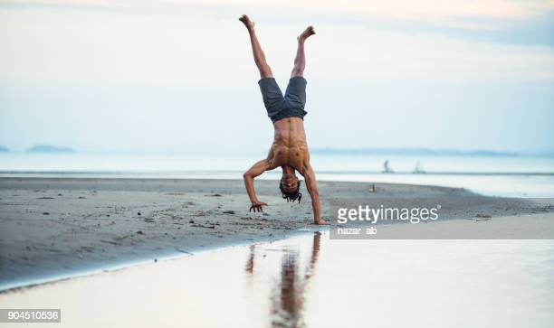 Man standing on one hand at beach.
