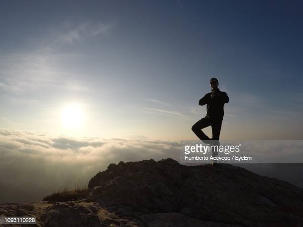 Man Standing On One Leg At Rock Against Sky During Sunset