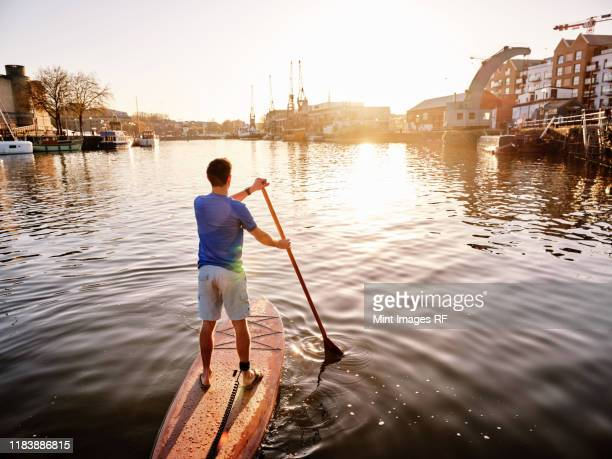 man standing on paddleboard on river at dawn, shot from behind - bristol stock pictures, royalty-free photos & images