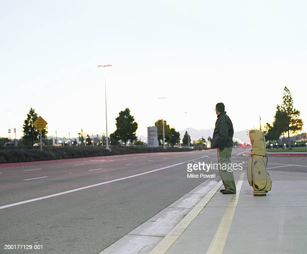 Man standing on pavement with golf bag