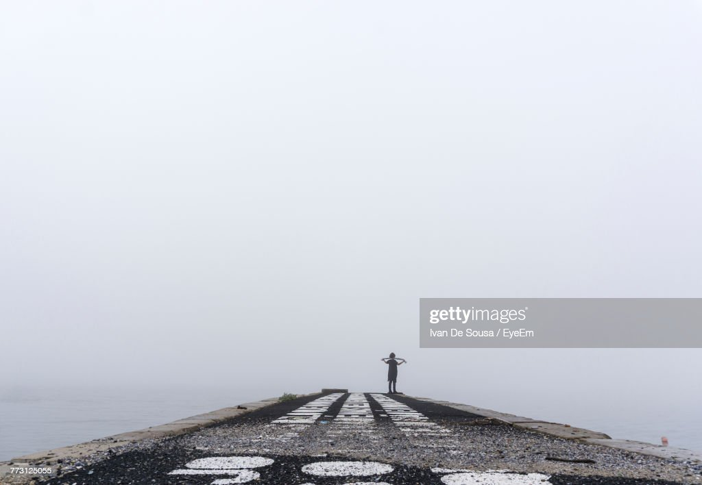 Man Standing On Pier Against Clear Sky : Photo