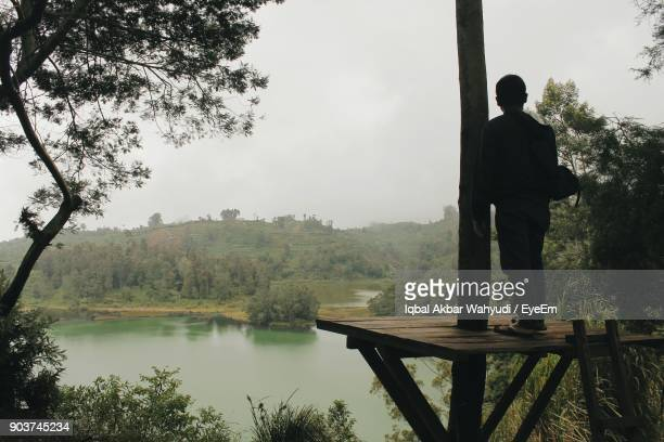 Man Standing On Pier By Lake Against Sky