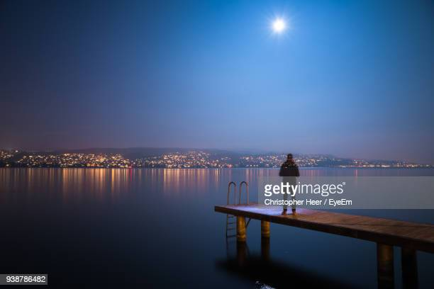 Man Standing On Pier Over Lake Against Illuminated City At Night