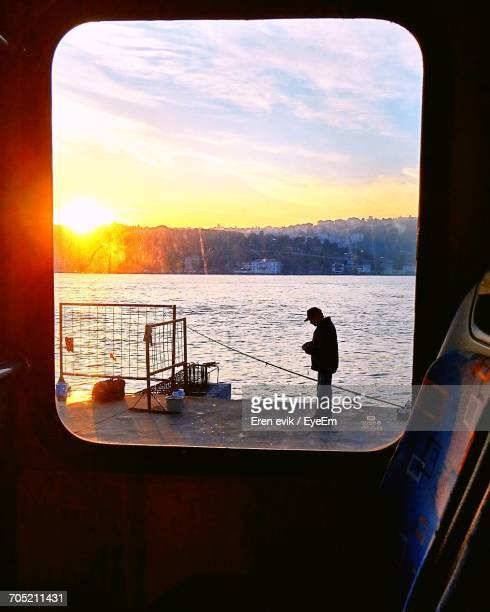 Man Standing On Pier Seen Through Boat Window During Sunset