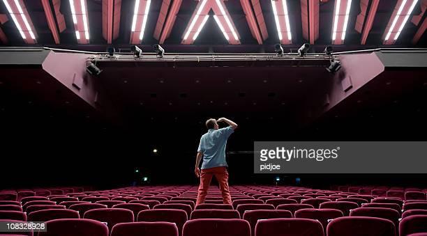 mann, stehend auf rotem samt seat starren in leere auditorium - zuschauerraum stock-fotos und bilder