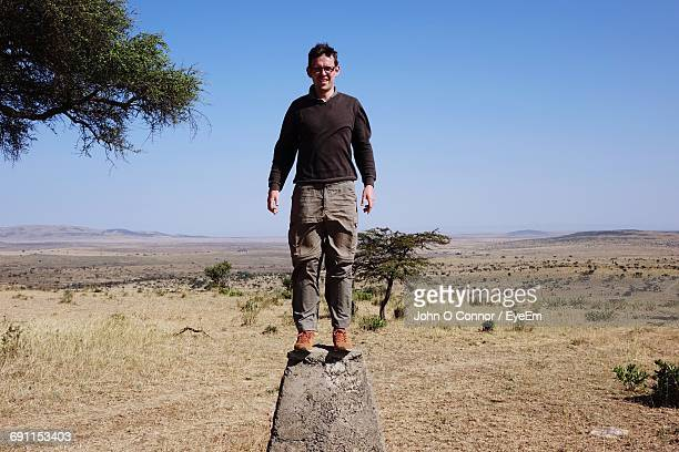 Man Standing On Retaining Wall Against Clear Sky