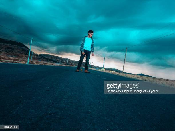 man standing on road against sky - casual chique ストックフォトと画像