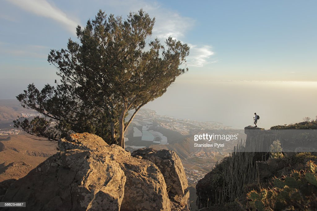 Man standing on rock above city and ocean : Stock Photo