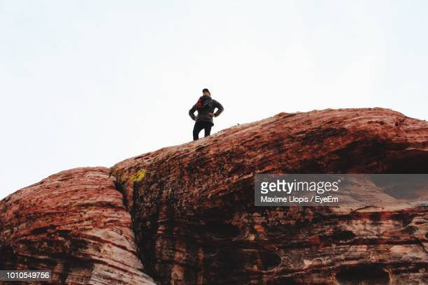 man standing on rock against clear sky - nevada stock-fotos und bilder