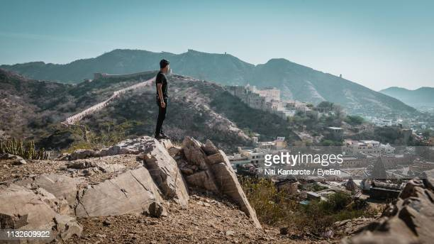 man standing on rock against clear sky - 南アジア ストックフォトと画像