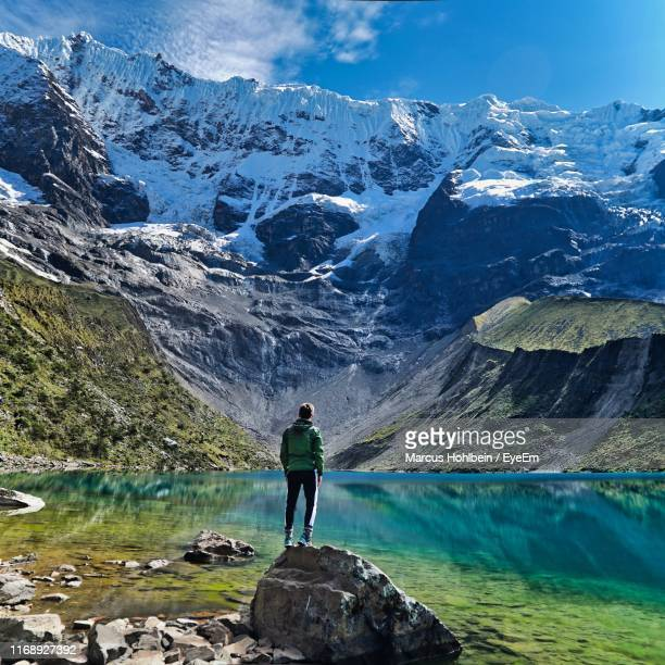 man standing on rock against mountains - buitensport stockfoto's en -beelden