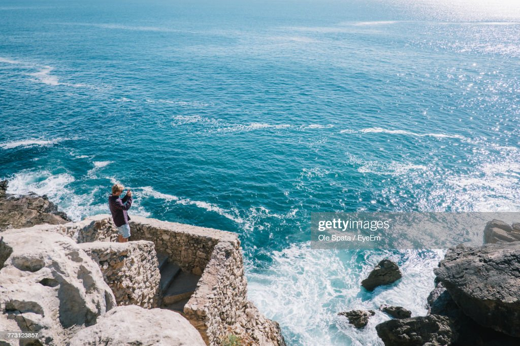 Man Standing On Rock Against Sea : Photo