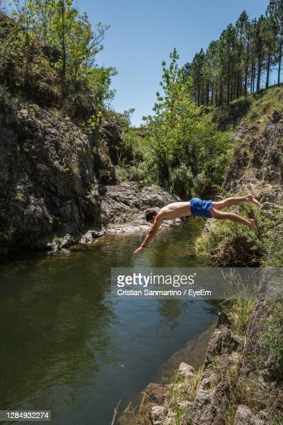 man standing on rock against trees - cordoba argentina stock pictures, royalty-free photos & images
