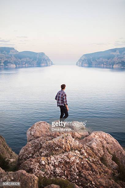 man standing on rock and looking out to sea - mid section stock photos and pictures