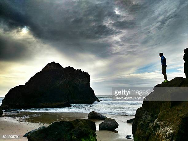 man standing on rock at beach against cloudy sky - grove stock photos and pictures