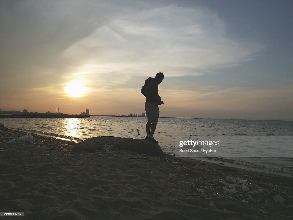 Man Standing On Rock At Beach Against Sky During Sunset : Stock Photo
