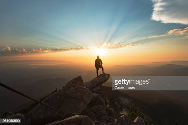 man standing on rock at cliff against sky during sunset - 立ち向かう ストックフォトと画像