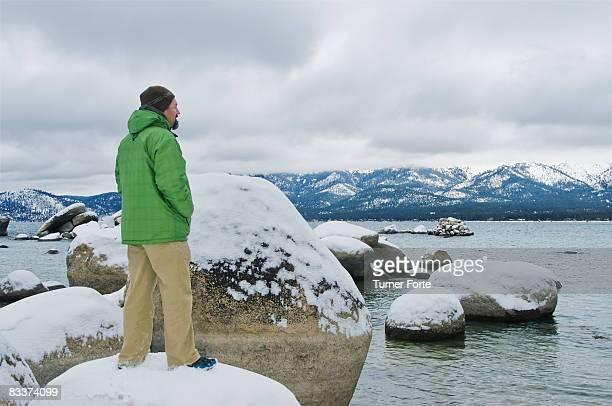 Man standing on rock at lake.