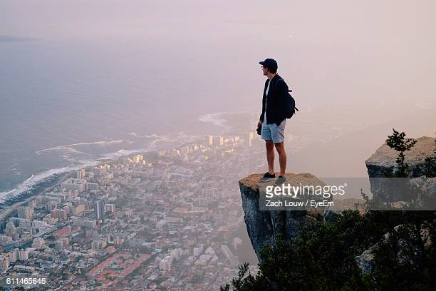 Man Standing On Rock At Mountain Peak Looking At Cityscape And Sea