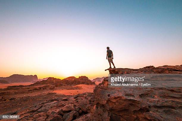 Man Standing On Rock At Wadi Rum Against Clear Sky