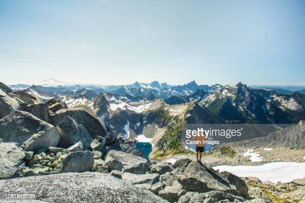 man standing on rock boulder with view of mountains, mount baker. - カスケード山脈 ストックフォトと画像