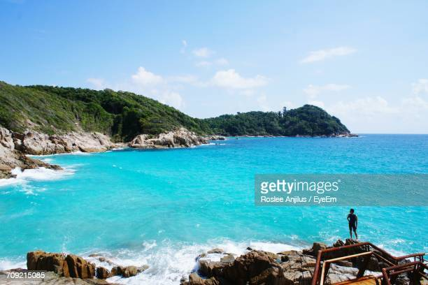 man standing on rock by blue sea against sky - terengganu stock pictures, royalty-free photos & images