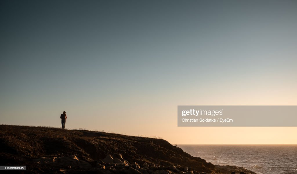 Man Standing On Rock By Sea Against Clear Sky : Stock-Foto