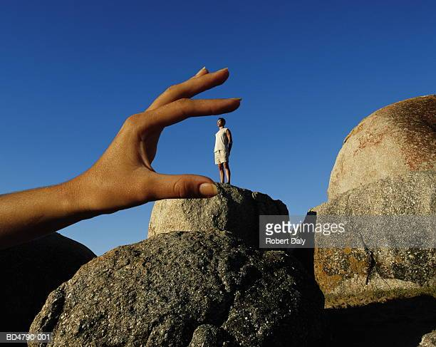 man standing on rock, hand sizing him in foreground (composite) - illusion stock pictures, royalty-free photos & images