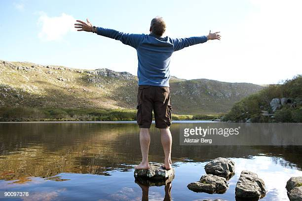man standing on rock in front of lake - pantaloncini foto e immagini stock