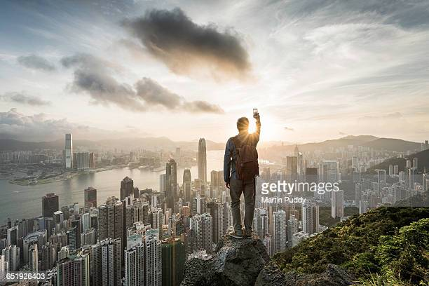 man standing on rock infront of Hong Kong skyline
