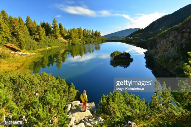 man standing on rock looking at beautiful mountain lake - pirin mountains stock pictures, royalty-free photos & images