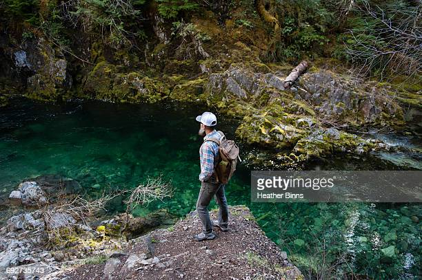 man standing on rock looking away at river, opal creek, oregon, usa - heather brooke ストックフォトと画像