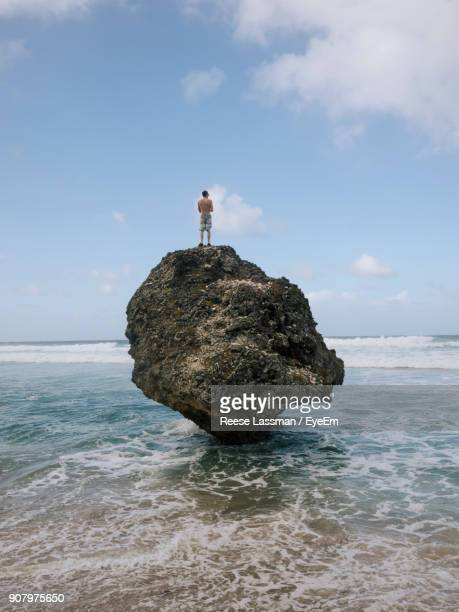 Man Standing On Rock Over Sea Against Sky