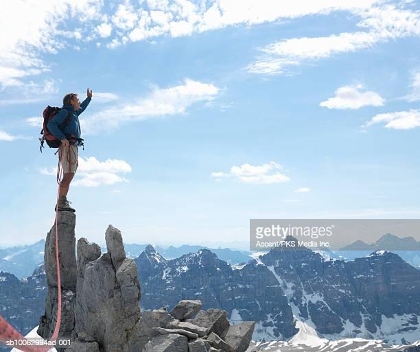 man standing on rock pinnacle, holding rope mad waving hand - pinnacle rock formation stock-fotos und bilder