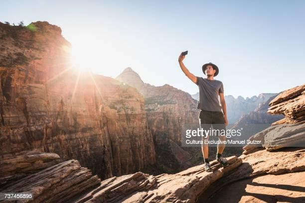 Man standing on rock, taking selfie, using smartphone, Zion National Park, Utah, USA